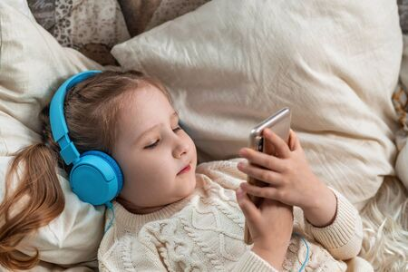 A little girl with headphones and holding a smartphone in her hands lies on the sofa and looks at the screen of her mobile phone. Close up. top view. Concept of leisure during the covid-19 quarantine