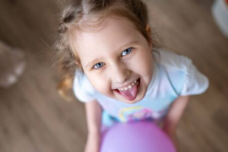 A cheerful little blonde girl with a balloon in her hands laughs and shows her tongue. Close up. The view from the top. The naughty child is very amused and teases with his tongue hanging out.