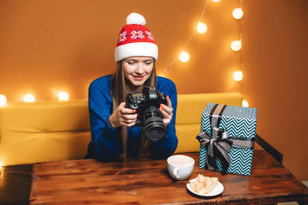 Beautiful woman in Christmas hat with professional digital camera in cafe Imagens - 134846519
