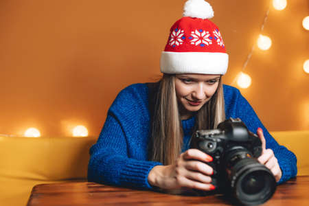 Beautiful woman in Christmas hat with professional digital camera in cafe