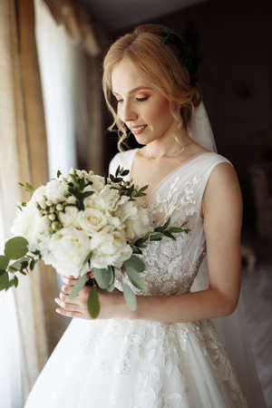 Beautiful bride portrait in wedding dress near window. High quality photo