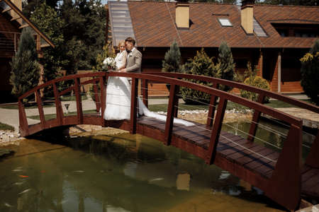 Beautiful wedding couple is standing on the wooden bridge. The bride in tulle veil and elegant hairdo is holding hands with her bearded groom in bow tie. Rustic outdoors stylish love story. High quality photo Standard-Bild