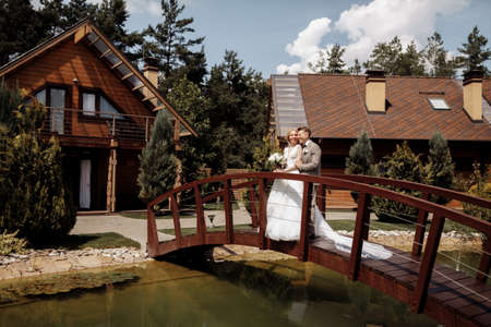 Beautiful wedding couple is standing on the wooden bridge. The bride in tulle veil and elegant hairdo is holding hands with her bearded groom in bow tie. Rustic outdoors stylish love story. High quality photo