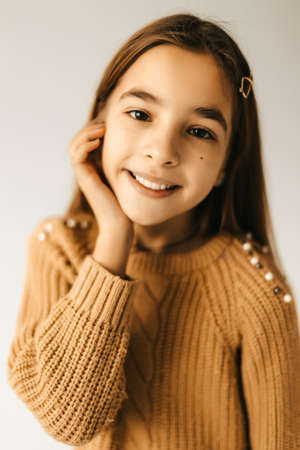 Portrait of a little beautiful girl smirking on a white background in a knitted sweater. High quality photo
