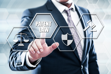 Business, technology, internet concept on hexagons and transparent honeycomb background. Businessman pressing button on touch screen interface and select patent law.