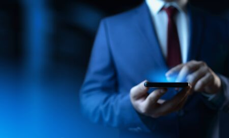 Businessman holding smartphone. Man using phone in office