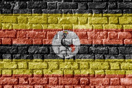 De Vlag van Oeganda die op bakstenen muur wordt geschilderd