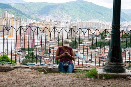 Caracas,Venezuela. Woman texting in El Calvario Park, Ezequiel Zamora Park.