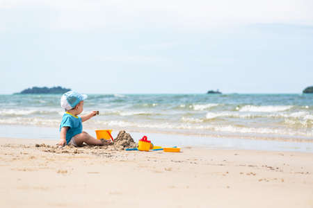 happy child playing on the beach in the summer sun