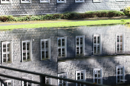 Reflection of a window front of a slate house  facade of slate in the water