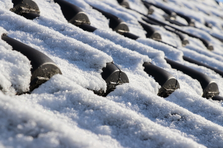 Black roof tiles  roof tiles covered with snow