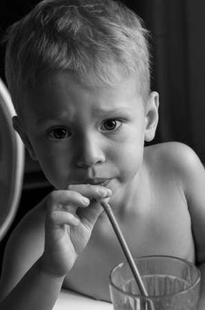 slurp: little boy drinks through straw. Drinking straw holding in his right hand. He looks into the camera. Emotion serious. BW.