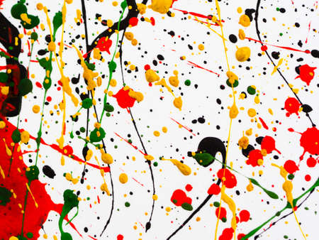 an abstraction with splashes of black and red and green and yellow paint on a white background