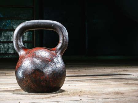 vecchio peso sportivo arrugginito in una palestra su un pavimento di legno