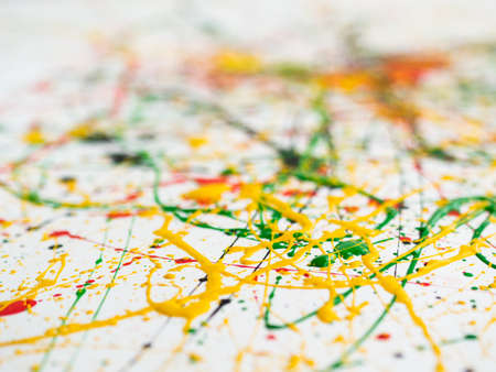 splashed of spilled yellow green red black paint. expressionism. View from the outside. Shallow depth of field