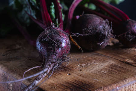 three unwashed juicy beets with green leaves lies on a wooden board. country style. rusty style. Horizontal orientation. ugly food. dark background. Reklamní fotografie