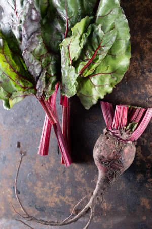 Beets and beet leaves on a rusty beautiful metal surface.