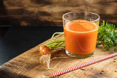 one litle ugly carrot. Glass with freshly squeezed carrot juice. one ugly carrot with green leaves. plastic free. cardboard tube. Wood background. horizontal orentecion. close up