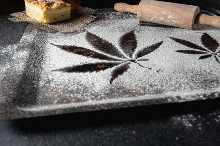 cooking cannabis food. Trail of cannabis leaf on white flour on a rust table. battledore. on a burlap treats a pie. Horizontal orientation.