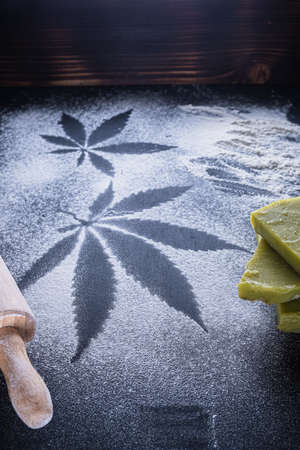 The process of making cannabis pastries. You can see a rolling pin, traces of marijuana leaves on flour, and tiles hashish oil. Vertical orientation