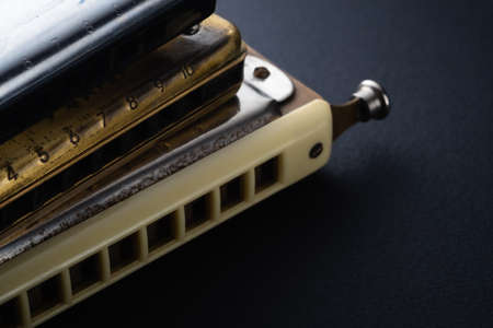 the old two diatonic and one chromatic harmonica, one on top of the other on a dark background. Horizontal orientation.