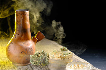 Steaming bong with medical cannabis on a wooden surface. Nearby is an open grinder and a marijuana bud. dark frame. horizontal orientation.