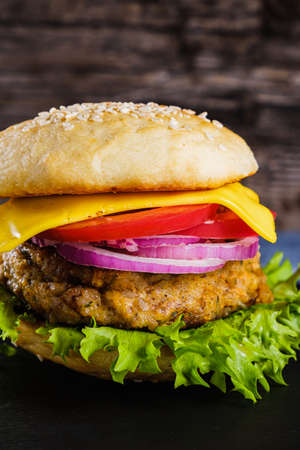 Fresh delicious homemade veggie burger lies on natural slate on rustic wooden background. Delicious tasty burger with lettuce, cheese, onion and tomato. buckwheat and lentil cutlet. Vertical orintation.