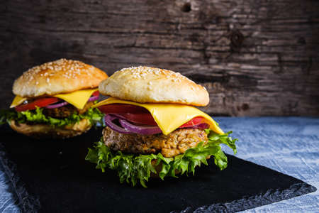 Two Fresh delicious homemade veggie burger lies on natural slate on rustic wooden background. Delicious tasty burger with lettuce, cheese, onion and tomato. buckwheat and lentil cutlet. horizontal orintation Stock fotó