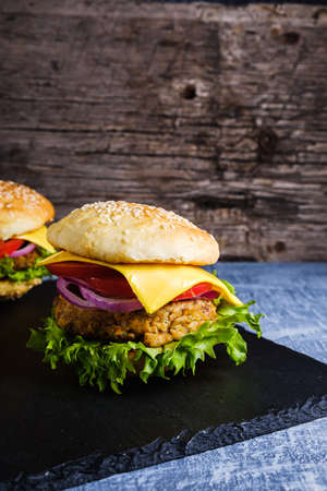 Two Fresh delicious homemade veggie burger lies on natural slate on rustic wooden background. Delicious tasty burger with lettuce, cheese, onion and tomato. buckwheat and lentil cutlet. Vertical orintation.