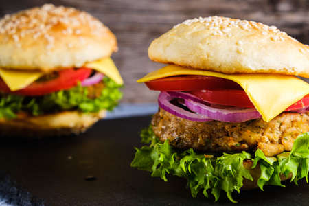 Two Fresh delicious homemade veggie burger lies on natural slate on rustic wooden background. Delicious tasty burger with lettuce, cheese, onion and tomato. buckwheat and lentil cutlet. horizontal orintation Stockfoto