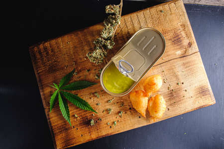 balls donuts from medical cannabis butter, sugar, flour, egg. marijuana buds. medical cannabis butter in a open tin can. hemp leaves. On a wooden board. horizontal orientation. top view