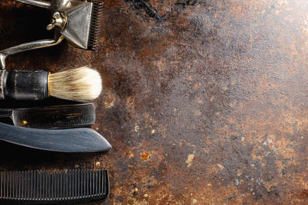 On a rusty surface are old hairdresser tools. manual clipper, comb, razor, shaving brush. rustic. horizontal. top view. flat ley. copy space. 免版税图像