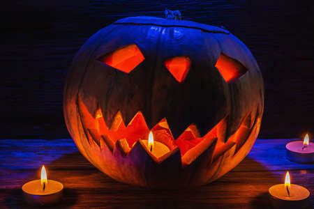 Jack O' Lantern Glowing In Fantasy Night. Halloween. candles are burning nearby. On old wooden background. dramatic frame. horizontal orientation