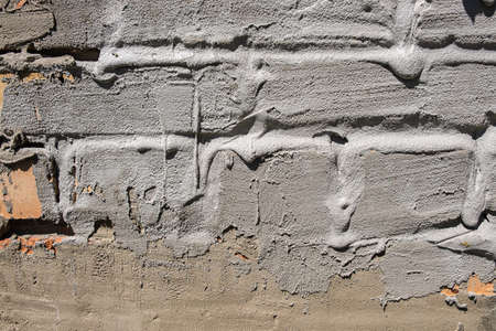 rough plastered brick wall. streaks of concrete. textured background. Different quality plaster Imagens