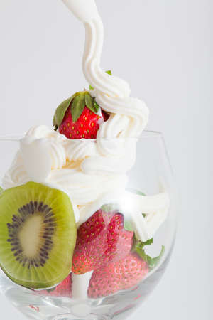 top: Ice cream in bowl with strawberry and kiwi