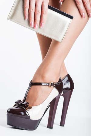 Frau trägt High Heels auf weißem Hintergrund