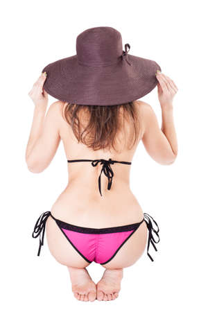 Back of young beautiful woman isolated on white background wearing summer beach hat and bikini photo