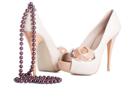 Biege high heel shoes and beads isolated on white photo