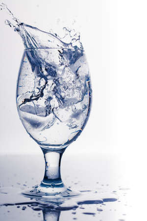 Splash from ice cube in a glass of water, isolated on the white background photo