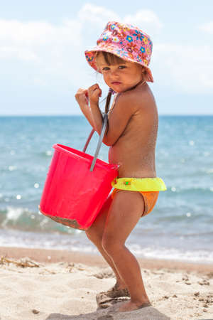 Vertical photo of toddler girl playing with toys at beach photo