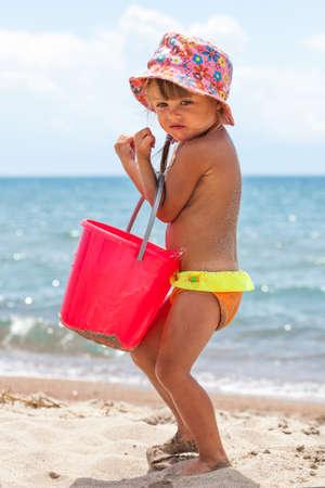 Vertikale Foto von Kleinkind Mädchen spielen mit Spielzeug am Strand
