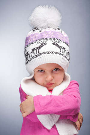 Portrait of an adorable baby girl wearing a knit pink and white winter hat   photo