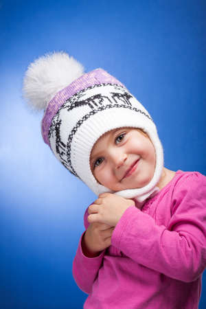 Portrait of an adorable baby girl wearing a knit pink and white winter hat   Stock Photo - 16466771