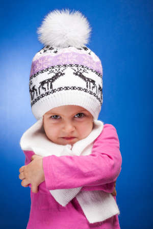Portrait of an angry baby girl wearing a knit pink and white winter hat. photo