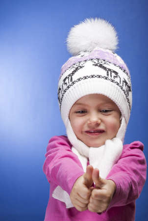 Portrait of an adorable baby girl wearing a knit pink and white winter hat.  photo