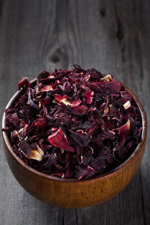 heap of hibiscus tea in a wooden bowl on old board photo