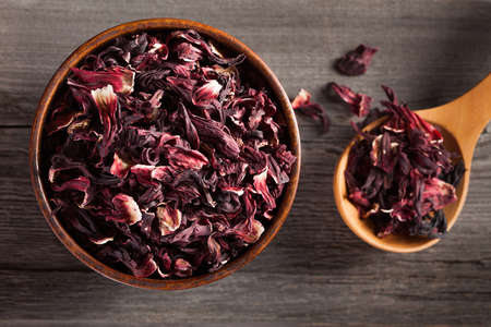 Bowl of aromatic Hibiscus tea with wooden spoon on wooden board Imagens