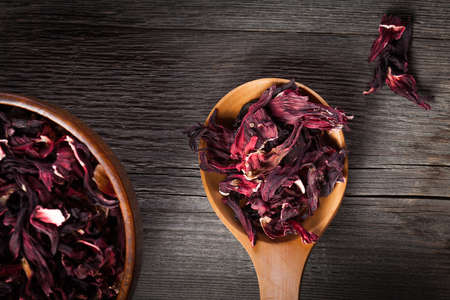 Bowl of aromatic Hibiscus tea with wooden spoon on wooden board photo