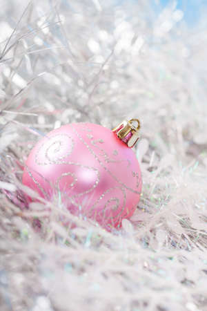 Pink xmas ornaments on bright holiday background