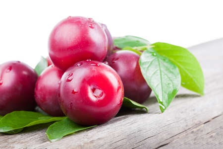 fresh plums with green leaves on wooden board